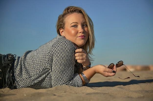 Retrato de una joven rubia posando en el mar con accesorios de moda gastados