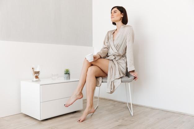 Retrato de una joven satisfecha vestida con bata de baño