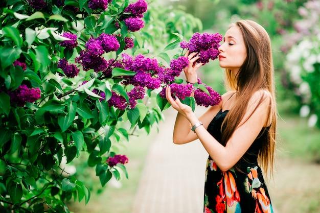 Retrato de joven sensual con el pelo largo disfrutando de anf relajante en el parque floreciente de primavera.