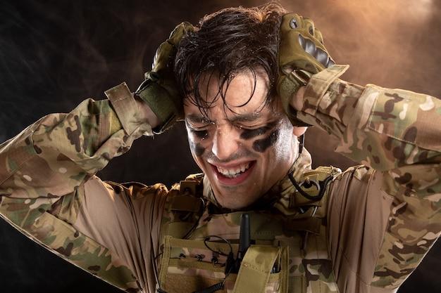 Retrato de joven soldado en camuflaje con dolor de cabeza en pared negra