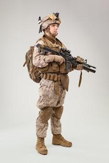 Retrato de un joven soldado estadounidense del cuerpo de marines de estados unidos sobre fondo gris