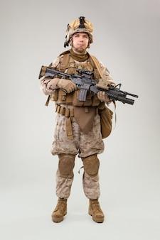 Retrato de un joven soldado estadounidense del cuerpo de marines de estados unidos sobre gris
