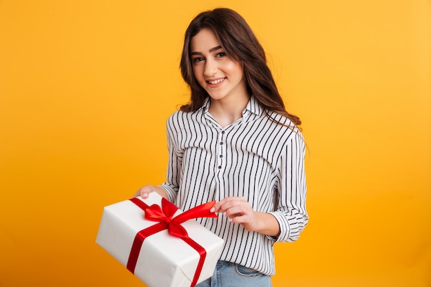 Retrato de una joven sonriente abriendo una caja de regalo