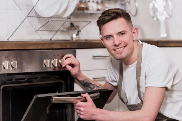 Retrato de un joven sonriente abriendo el horno en la cocina