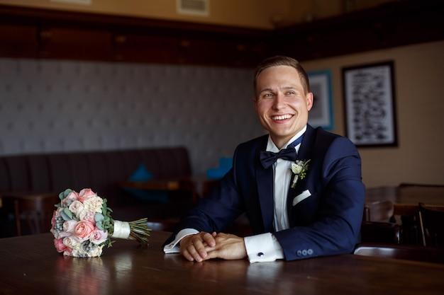 Retrato de joven sonriente en camisa blanca y chaqueta negra con una mariposa negra. chico de traje oscuro con ramo de novia en elegante interior.