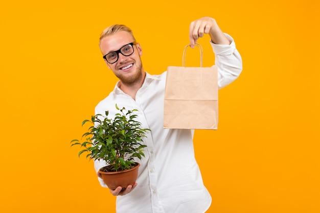 Retrato de un joven sonriente en una camisa de vestir blanca y gafas sosteniendo una bolsa de artesanía y una planta de interior en una maceta en un amarillo