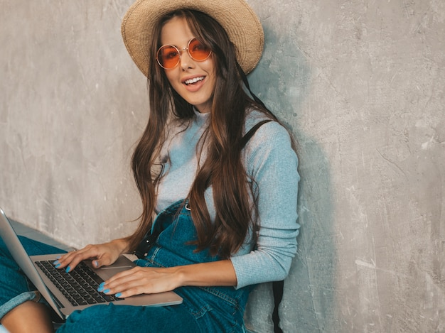 Retrato de joven sonriente creativa en gafas de sol. hermosa niña sentada en el piso cerca de la pared gris.