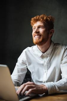 Retrato de un joven sonriente escribiendo en una computadora portátil