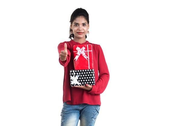 Retrato de joven sonriente feliz celebración y posando con cajas de regalo sobre un fondo blanco.
