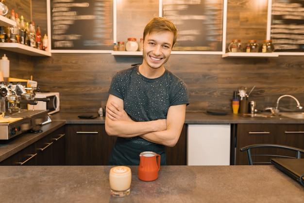 Retrato de joven sonriente hombre trabajador de café, de pie en el mostrador