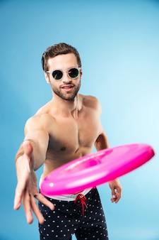 Retrato de un joven sonriente lanzando frisbee