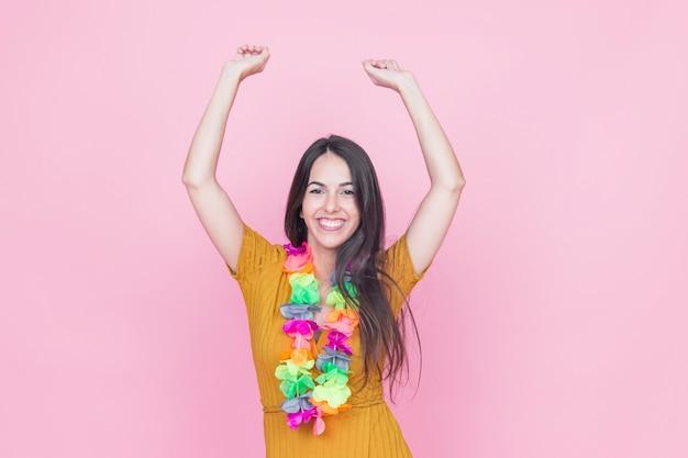 Retrato de una joven sonriente, levantando los brazos sobre fondo rosa