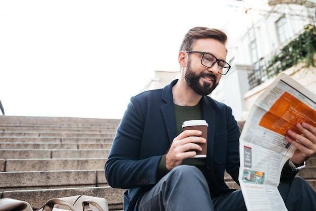 Retrato de un joven sonriente leyendo el periódico
