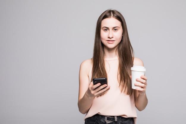Retrato de una joven sonriente en mensaje de texto de camisa en teléfono móvil y sosteniendo una taza de café para ir aislado sobre la pared gris