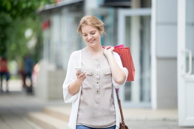 Retrato de joven sonriente mirando el teléfono mientras va de compras