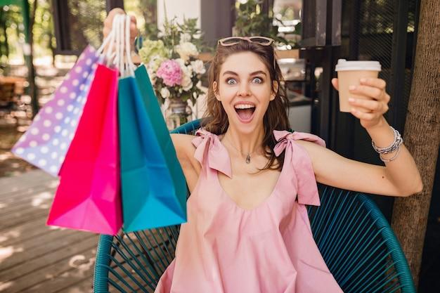 Retrato de joven sonriente mujer bonita feliz con expresión de la cara emocionada sentado en la cafetería con bolsas de compras tomando café, traje de moda de verano, vestido de algodón rosa, ropa de moda