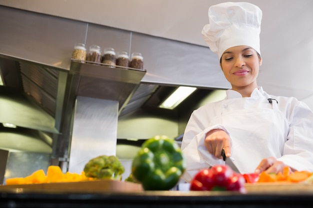 Retrato de una joven sonriente mujer chef cortar verduras en la cocina