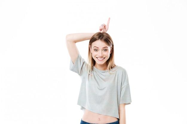 Retrato de una joven y sonriente mujer joven sosteniendo el dedo
