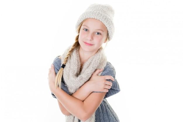 Retrato de joven sonriente mujer de pie con las manos juntas sobre fondo blanco y gorro de lana bufanda