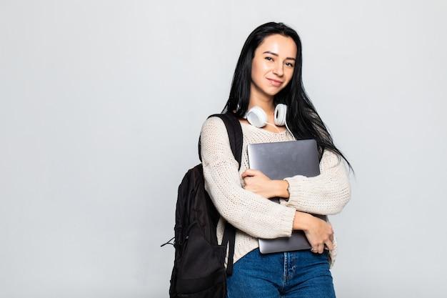 Retrato de una joven sonriente de pie con la computadora portátil contra la pared gris