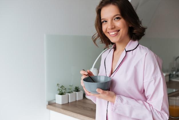 Retrato de una joven sonriente en pijama desayunando