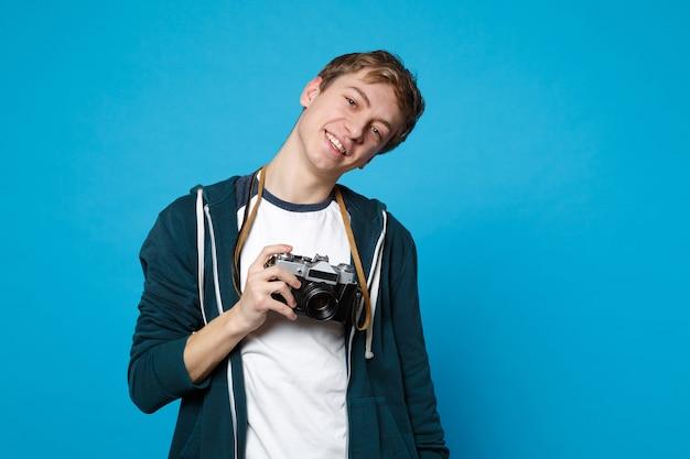 Retrato de joven sonriente en ropa casual sosteniendo en las manos cámara de fotos vintage retro aislada en la pared azul. personas sinceras emociones, concepto de estilo de vida.