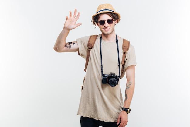 Retrato de un joven sonriente con sombrero y mochila agitando su mano sobre fondo blanco.