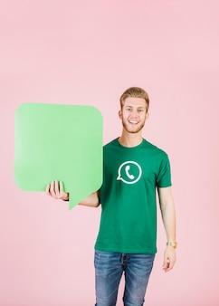 Retrato de un joven sonriente sosteniendo el bocadillo de diálogo verde vacío