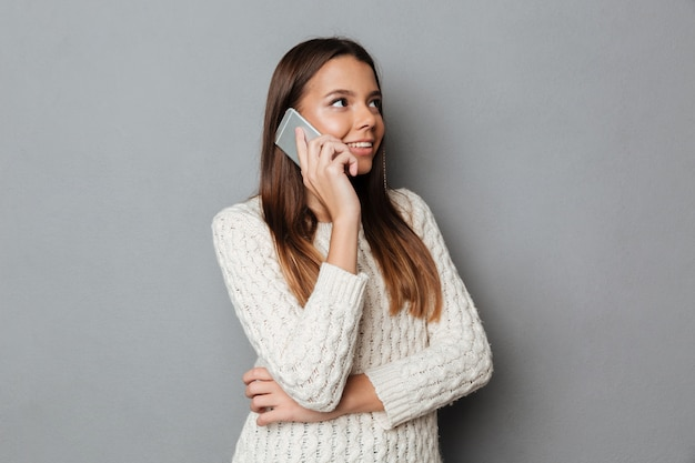 Retrato de una joven sonriente en suéter hablando