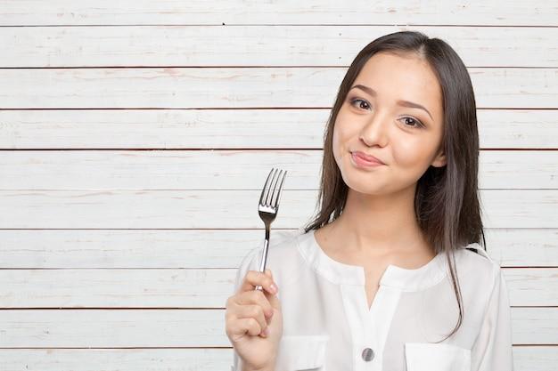 Retrato de joven sonriente con tenedor en su boca
