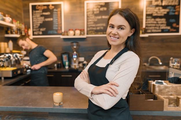 Retrato de joven sonriente trabajadora de café, de pie en el mostrador
