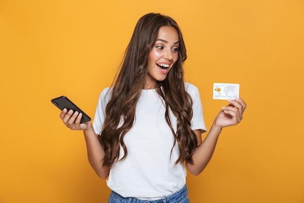 Retrato de una joven sorprendida con cabello largo morena de pie sobre una pared amarilla, sosteniendo un teléfono móvil, mostrando una tarjeta de crédito de plástico