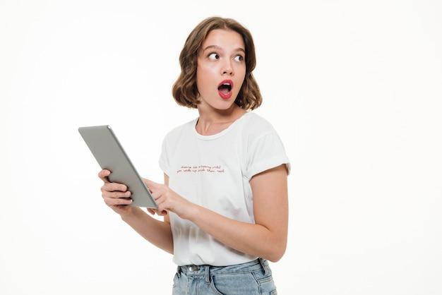 Retrato de una joven sorprendida con tablet pc