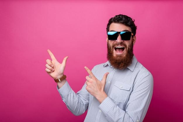 Retrato de joven sorprendido con barba apuntando lejos a copyspace