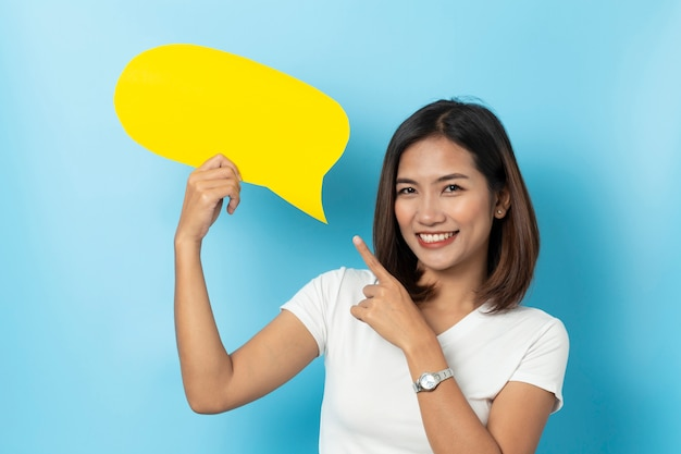 Retrato de joven sosteniendo un bocadillo de diálogo amarillo vacío aislado en azul
