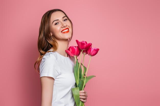 Retrato de una joven sosteniendo un ramo de tulipanes y sonriendo aislado sobre un fondo rosa