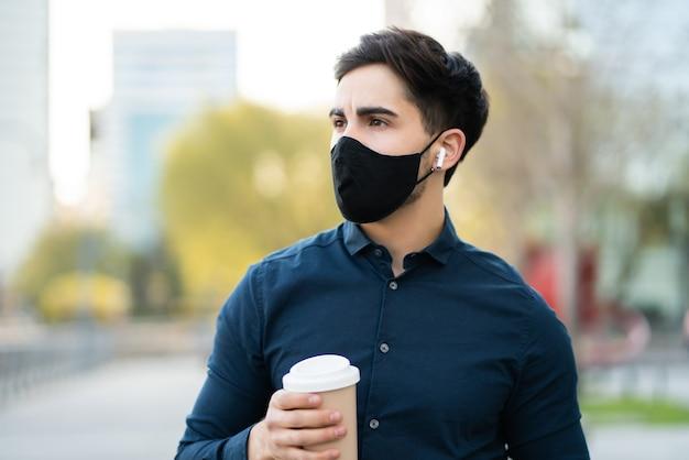 Retrato de joven sosteniendo una taza de café mientras está parado al aire libre en la calle. nuevo concepto de estilo de vida normal.