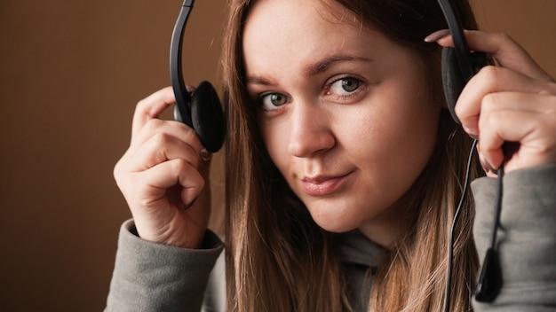 Retrato de una joven con una sudadera con capucha y con un trabajador del centro de llamadas de auriculares