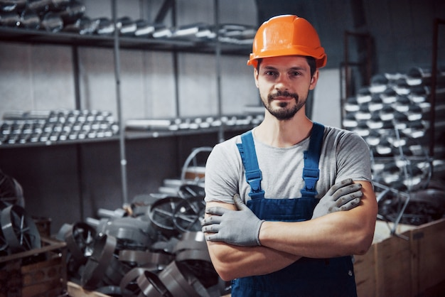 Retrato de un joven trabajador con un casco en una gran planta metalúrgica.