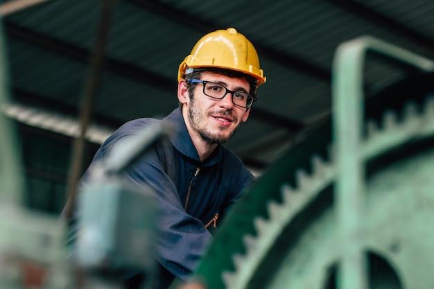 Retrato de joven trabajador feliz estadounidense disfruta feliz sonriendo a trabajar en una fábrica industrial pesada.