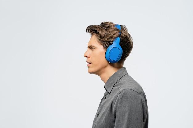 Retrato de un joven en traje gris de pie de lado escuchando música con auriculares inalámbricos azules