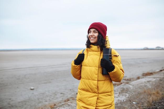 Retrato de una joven turista con una mochila caminando por la calle lateral entre las vastas tierras bajas del valle de invierno vacío. viajero mujer vestida con chaqueta amarilla y sombrero rojo. autostop, concepto de viaje.