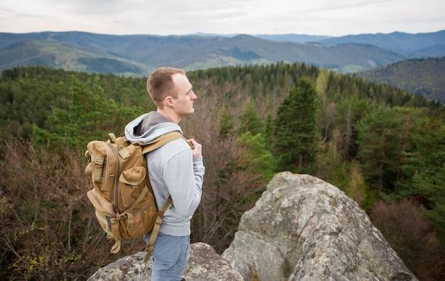 Retrato de joven turista con mochila se coloca encima de la roca