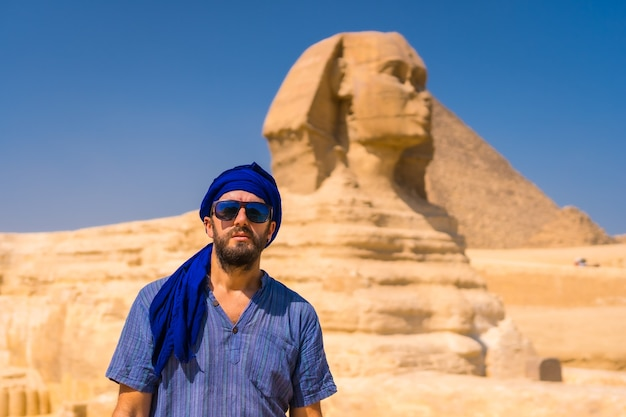 Retrato de un joven turista vestido de azul y un turbante azul en la gran esfinge de giza. el cairo, egipto