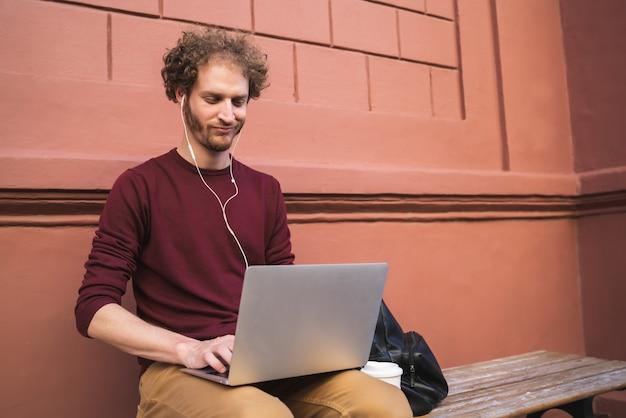 Retrato de joven usando su computadora portátil mientras está sentado al aire libre
