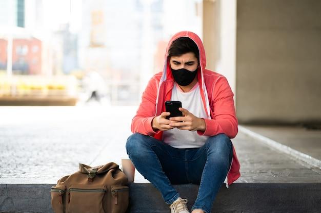 Retrato de joven usando su teléfono móvil mientras está sentado al aire libre en la calle. hombre vestido con mascarilla. concepto urbano.