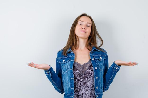 Retrato de jovencita haciendo gestos de escamas en blusa, chaqueta vaquera y mirando alegre vista frontal