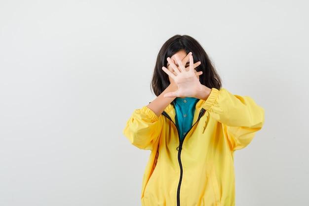 Retrato de jovencita mostrando gesto de parada, sosteniendo la mano en la cara con chaqueta amarilla y mirando asustado vista frontal