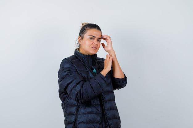 Retrato de jovencita posando mientras toca la cabeza en chaqueta acolchada y mirando elegante vista frontal