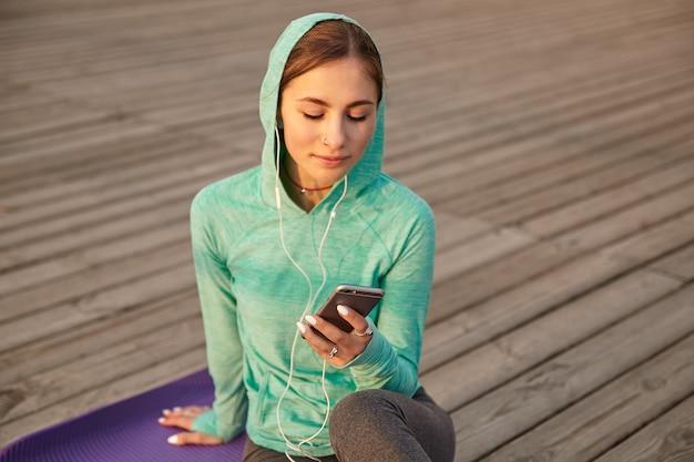 Retrato de jovencita en ropa deportiva brillante, escuchando su canción favorita en auriculares después de yoga matutino y charlando con amigos.